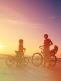 Madre con los niños biking en la puesta del sol Foto de archivo libre de regalías
