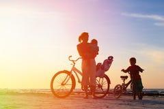 Madre con los niños biking en la puesta del sol Fotografía de archivo