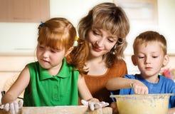 Madre con los niños en cocina Foto de archivo