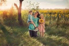Madre con los niños en girasoles Foto de archivo libre de regalías