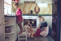Madre con los niños en la cocina Fotos de archivo libres de regalías