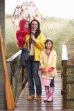 Madre con los niños en la playa imagenes de archivo