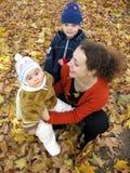 Madre con los niños en las hojas de otoño Foto de archivo