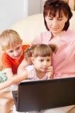 Madre con los niños en una computadora portátil imágenes de archivo libres de regalías