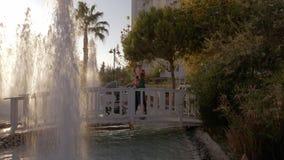 Madre con los niños que caminan en jardín del hotel con las fuentes almacen de metraje de vídeo
