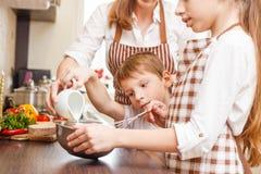 Madre con los niños que cocinan el huevo revuelto Imagen de archivo