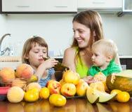 Madre con los niños que comen los melocotones Imagenes de archivo