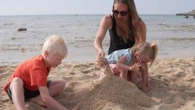 Madre con los niños que construyen un castillo de la arena en la playa almacen de metraje de vídeo