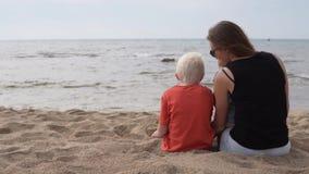 Madre con los niños que disfrutan de la vista del mar almacen de video