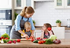 Madre con los niños que preparan la ensalada vegetal Imagen de archivo