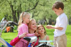 Madre con los niños y la bicicleta en parque fotografía de archivo