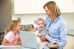 Madre con los niños que usan la computadora portátil en cocina Imagen de archivo