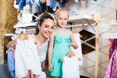 Madre con los pijamas de compra del bebé de la hija en la sección de los niños Fotografía de archivo libre de regalías