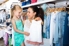 Madre con los pijamas de compra del bebé de la hija rubia en la sección de los niños Foto de archivo libre de regalías