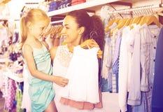 Madre con los pijamas de compra del bebé de la hija rubia en la sección de los niños Imagen de archivo libre de regalías