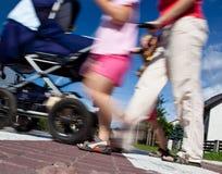 Madre con pequeños niños y un cochecito de niño que cruza una calle Fotografía de archivo libre de regalías