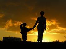 Madre con puesta del sol del hijo Imagen de archivo libre de regalías