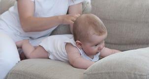 Madre con su bebé lindo en el sofá almacen de metraje de vídeo