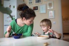 Madre con su bebé que come la sopa en la cocina brillante en casa Imagenes de archivo