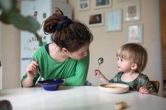 Madre con su bebé que come la sopa en la cocina brillante en casa Fotos de archivo libres de regalías
