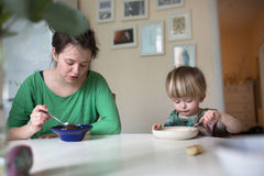 Madre con su bebé que come la sopa en la cocina brillante en casa Foto de archivo