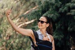 Madre con su beb? en el portador de beb? que toma el selfie con smartphone o el blogger foto de archivo