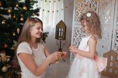 madre con su guirnalda de la Navidad del control de la hija de estrellas en sus manos Foto de archivo libre de regalías