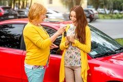 Madre con su hija cerca del coche rojo Imagen de archivo libre de regalías