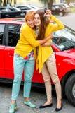 Madre con su hija cerca del coche rojo Imagen de archivo