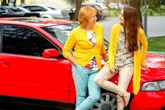 Madre con su hija cerca del coche rojo Fotografía de archivo