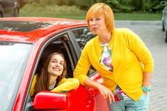 Madre con su hija cerca del coche rojo Imagenes de archivo