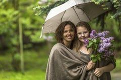 Madre con su hija en el parque en la lluvia junto debajo de un paraguas Famely Imagen de archivo