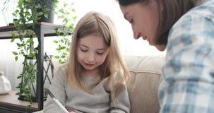 Madre con su hija que usa la pluma en casa almacen de video