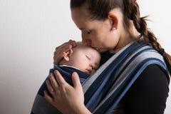 Madre con su hijo del bebé que duerme en honda Tiro del estudio imágenes de archivo libres de regalías