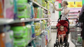 Madre con su muchacho en carro de bebé en el supermercado metrajes