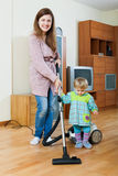 Madre con su niño que hace la limpieza casera Imagen de archivo libre de regalías