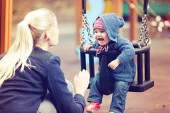 Madre con su niño que se divierte en el oscilación del patio imagen de archivo