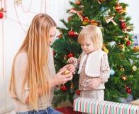 Madre con su pequeña hija debajo del árbol de navidad Imagenes de archivo