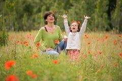 Madre con su pequeña hija en campo de la amapola Foto de archivo libre de regalías