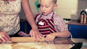 Madre con su pequeño hijo que prepara una pasta para el pan de jengibre de la Navidad almacen de video
