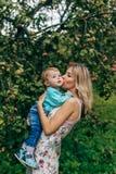 Madre con suo figlio sotto di melo fotografia stock