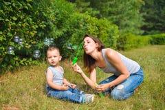Madre con sus burbujas que soplan del hijo en el día de verano Fotografía de archivo