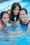 Madre con sus hijas en la piscina. Fotos de archivo