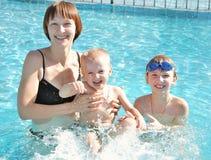 Madre con sus hijos en la piscina Foto de archivo