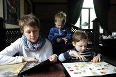 Madre con sus hijos en restaurante Imagen de archivo libre de regalías