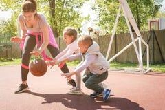 Madre con sus niños que juegan a baloncesto Imágenes de archivo libres de regalías