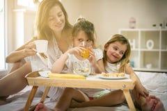Madre con sus pequeñas hijas que desayunan Fotos de archivo