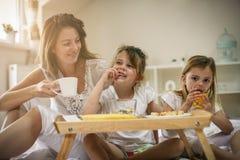 Madre con sus pequeñas hijas que desayunan en la cama Foto de archivo libre de regalías