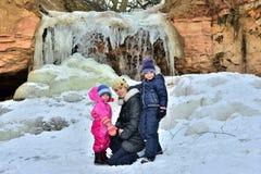 Madre con sus pequeñas hijas que presentan cerca de la cascada congelada, invierno Imágenes de archivo libres de regalías