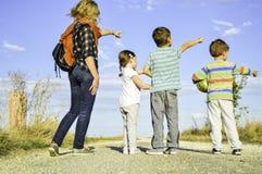 Madre con sus tres niños que caminan en familia en el campo y que señalan en algo en el camino imagenes de archivo